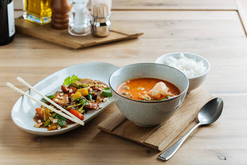 Top view of colorful vegetables in oval plate with chopsticks on wooden table with spicy seafood soup and with of boiled rice - ADSF14749