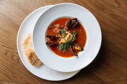 Top view of white round plate with rich spicy tomato soup with black mussels and seafood garnished with chopped greens - ADSF14764