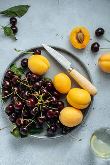 Flat lay of delicious cherry and yellow peach served on plate on a white background. - ADSF14767