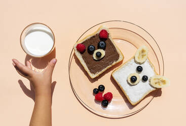 Studio shot of toasts with bear faces made of fruits and hand of baby girl reaching for glass of milk - GEMF04139