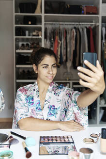 Young woman taking selfie on smart phone while sitting at home - JMHMF00092