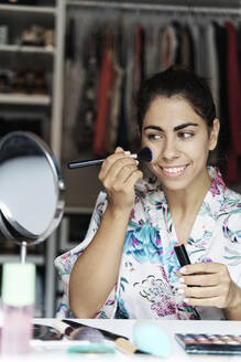 Smiling young woman applying blusher on face while looking at mirror - JMHMF00095