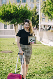 Smiling beautiful woman with suitcase holding box while standing on grassy land in park - DCRF00785