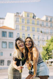 Cheerful female friends holding beer bottles while standing against building in city - DCRF00788