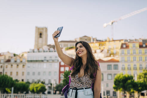 Smiling beautiful woman taking selfie with smart phone while standing in city - DCRF00797