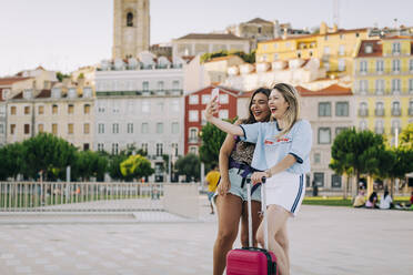 Cheerful tourist taking selfie with female friend while standing on footpath in city - DCRF00806