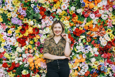 Smiling young woman standing against colorful flowers - DCRF00809