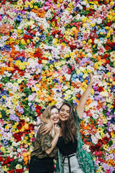 Cheerful female friends embracing while standing against colorful flowers - DCRF00812