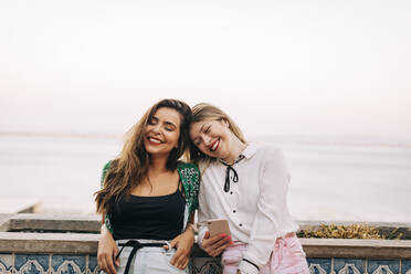 Smiling female friends with eyes closed sitting against sea - DCRF00818