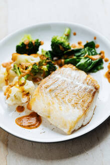 Appetizing fresh fish with green and broccoli sprinkled with red sauce on white plate - ADSF14838