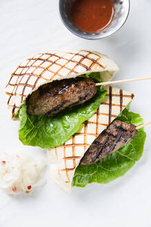 Fresh lettuce leaf and minced meat kebab wrapped in grilled tortilla and placed near cup with spicy sauce on cafe table - ADSF14856