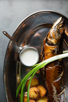 Top view of yummy roasted fish and potatoes served with ripe scallion and cream sauce on metal plate in restaurant - ADSF14859