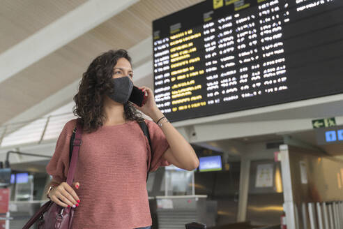 Young woman with protective face mask talking on smart phone while standing at airport - MTBF00661