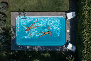 From above drone view of relaxed young female friends lying on water in pool and enjoying summer vacation while spending time together in green yard - ADSF14889