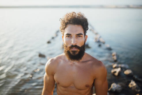 Shirtless bearded man standing against lake - MIMFF00185