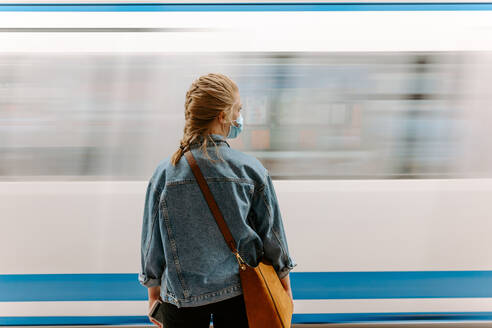 Back view of millennial female passenger in protective mask and casual denim jacket with handbag standing on underground platform in front of moving train - ADSF14970