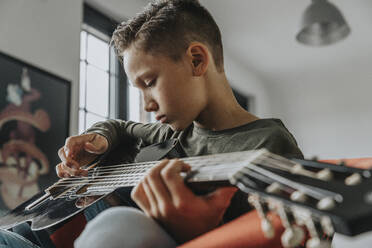 Close-up of boy playing guitar while sitting at home - MFF06115