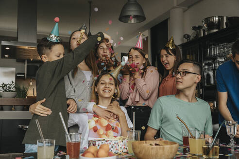 Happy friends throwing confetti on teenage girl in birthday party at home - MFF06124