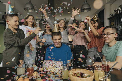 Cheerful friends throwing confetti on birthday boy sitting with gift at dining table - MFF06127