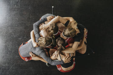 Girls huddling while crouching on floor in health club - MFF06166