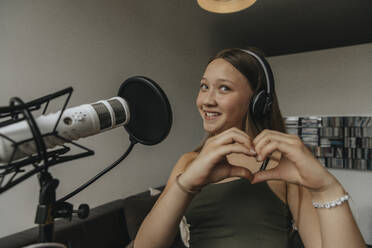 Smiling teenage girl making heart shape while singing in recording studio - MFF06172