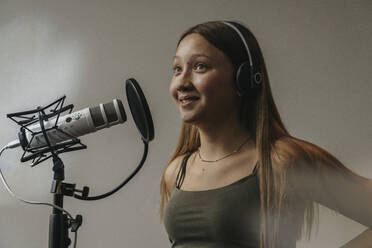 Close-up of smiling teenage girl singing over microphone against wall in recording studio - MFF06175
