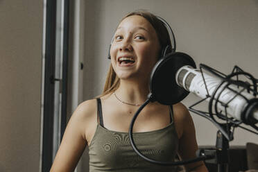 Close-up of teenage girl singing over microphone in studio - MFF06178