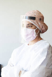 Orthodontist in protective suit standing with arms crossed at office - JCMF01278