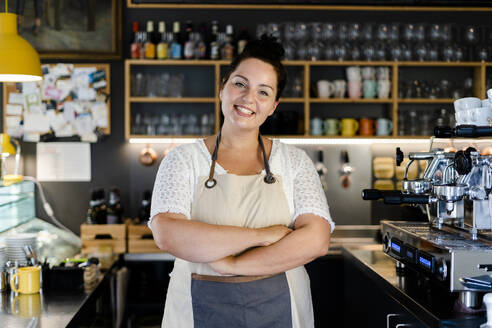 Smiling female barista with arms crossed standing in coffee shop - GIOF08763