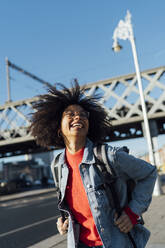 Cheerful young woman with afro hair standing against bridge in city on sunny day - BOYF01448