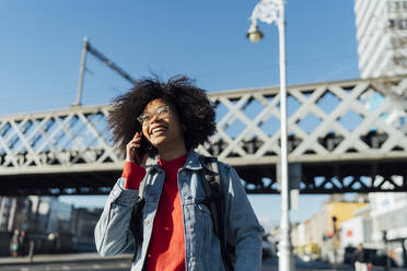 Cheerful afro young woman talking over smart phone while standing against bridge in city - BOYF01451