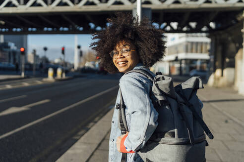 Smiling afro woman with backpack standing on sidewalk in city during sunny day - BOYF01457