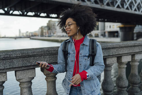 Afro young woman listening music through headphones while standing by railing on footbridge - BOYF01463
