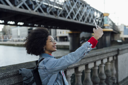 Afro young woman taking selfie with smart phone while standing by railing in city - BOYF01466