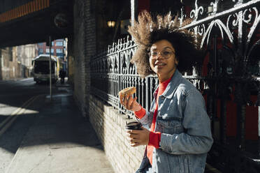 Young woman with afro hair holding donut and coffee while standing by fence in city - BOYF01472