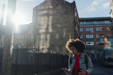 Afro young woman using smart phone while standing against buildings in city - BOYF01493
