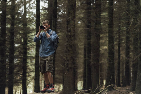 Male hiker photographing with camera while standing against trees in forest - BOYF01547