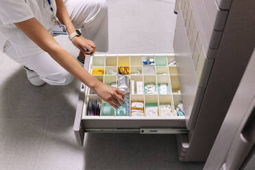 Female doctor searching medicines in drawer at pharmacy - DGOF01313