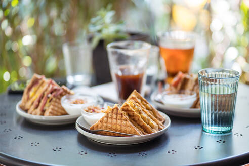 Delicious sandwiches on plate and refreshing drinks in glasses placed on table on summer terrace of cafe - ADSF15012