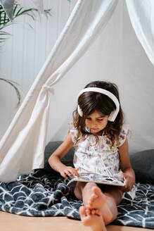 Full length concentrated barefoot female child in casual clothes sitting on blanket on wooden floor and using tablet and headphones in home tent - ADSF15077