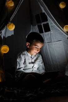 Full length happy boy in casual clothes sitting on blanket watching video on tablet in homemade tent decorated with garland with big lights in moon shapes in darn room at night - ADSF15083
