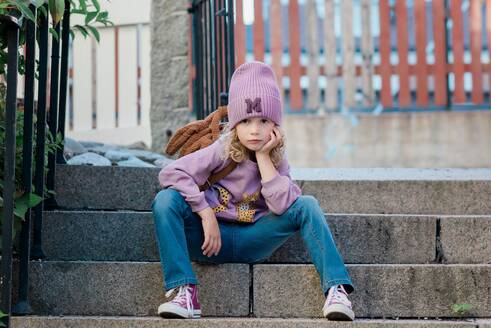 Portrait of a young girl sat on a step with attitude waiting - CAVF88764