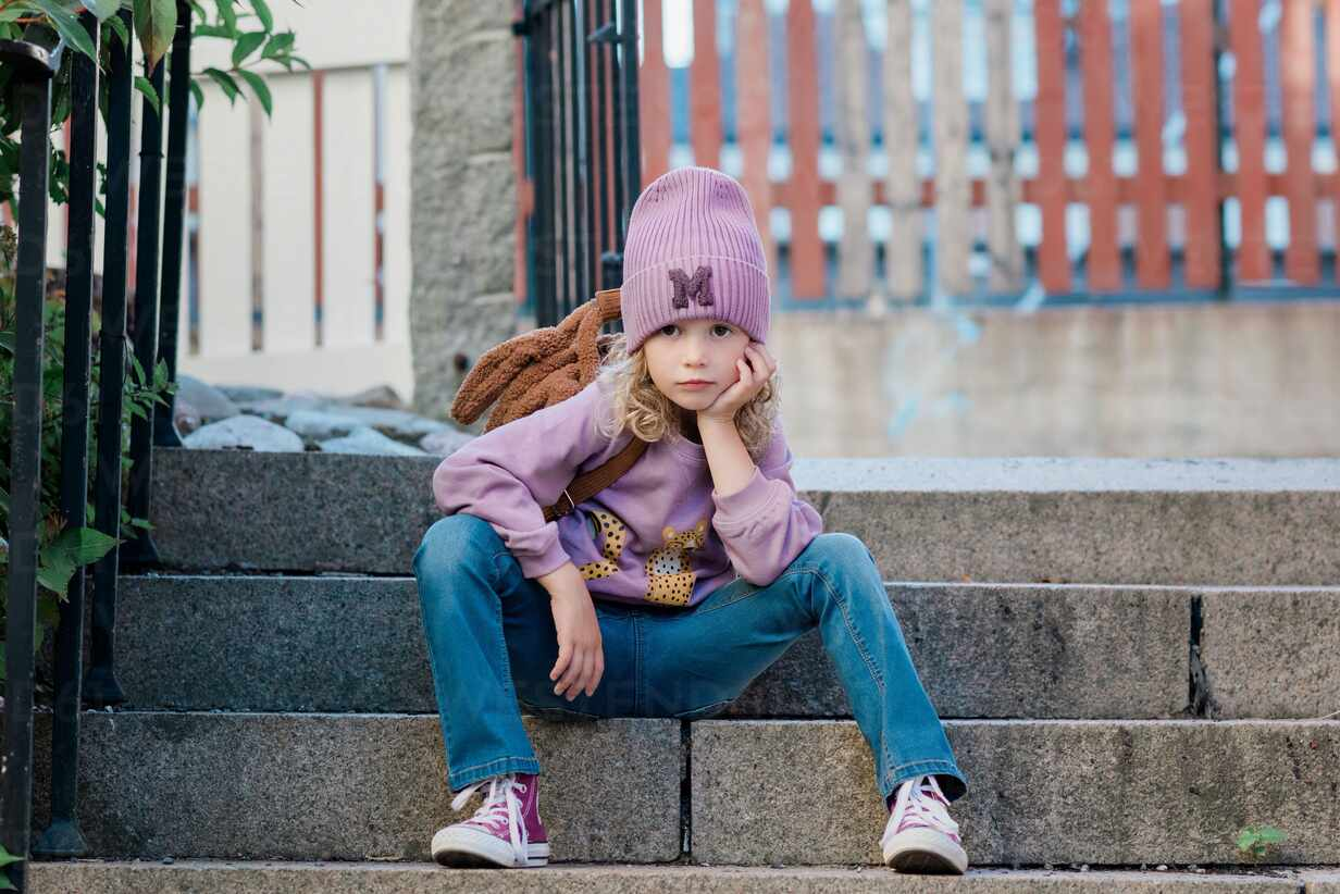 Portrait of a young girl sat on a step with attitude waiting - CAVF88764 - Cavan Images/Westend61