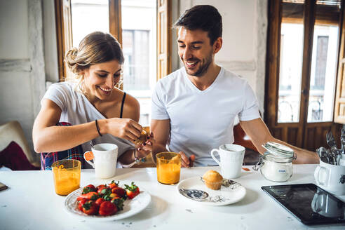 Young happy couple sitting by table in modern apartment and having breakfast together - EHF00897