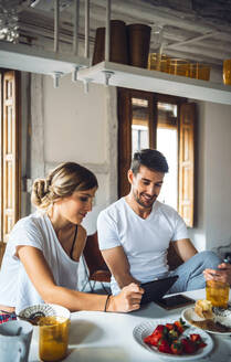 Beautiful couple in pajamas using tablet while having breakfast. - EHF00909