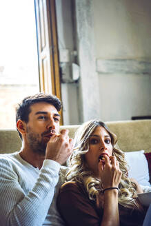 Young beautiful couple eating popcorn and watching movie. - EHF00927