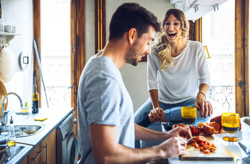 Young beautiful female laughing widely and sitting at kitchen with man cooking dinner. - EHF00930