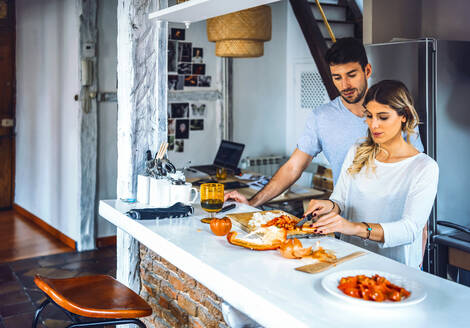 Young couple standing at kitchen and concentrated on cooking dinner. - EHF00939
