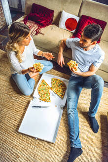 From above shot of young casual couple sitting on floor of living room and eating pizza. - EHF00951