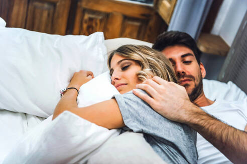 Young lovely couple lying in bed and hugging sensually. - EHF00984